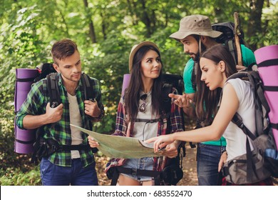 Four tourists got lost in the forest, holding map, trying to find the way, disscus it, all having backpacks, mates, all needed for overnight stay