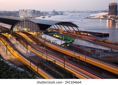 Four trains coming in Amsterdam Central Station at dusk, the golden hour, leaving light trails with the Amstel river and the city in the background, in Amsterdam, capital of the Netherlands