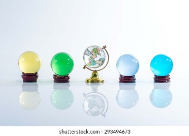 Four Transparent glass balls, spheres color, and Miniature world on white background.
