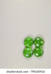 four transparent green decorative pebbles on a white background