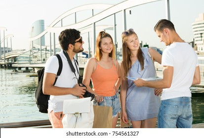 Four travelers holding map in hands and looking for their way in european town on summer day