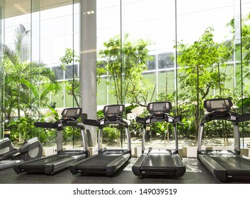 Four Treadmill in a gym with high ceiling in front of a big glass window