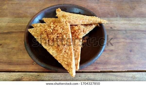 Four triangular slices of deep fried tempeh in Java, Indonesia