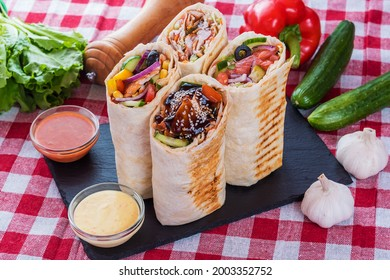 Four types of shawarma, doner in the composition of vegetables. Teriyaki, salmon, classic, burrito.