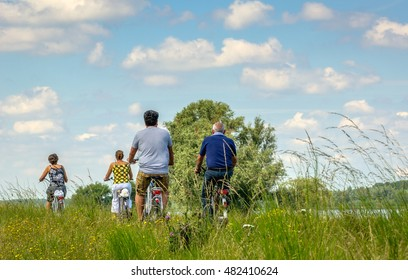 Four unknown people driving on a bike on a narrow trail between the high grass on an embankment beside a wide river in the Netherlands. It's a sunny day in the summer season.