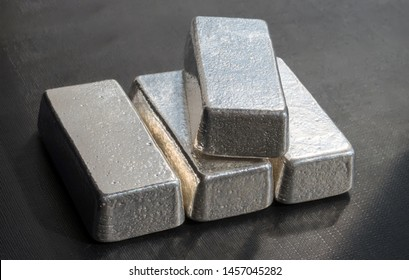 Four unmarked silver bars on a dark background. Selective focus.