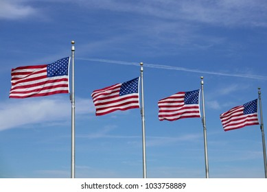 Four US flags waving against blue sky at the Washington Monument