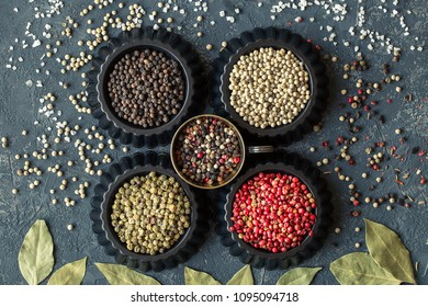 Four variations of peppercorns on dark stone table. Spice  background.  set of condiments. Ingredients for cooking. Food background  Top view,  copy space
