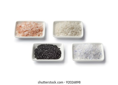 Four various types of salt in white dishes close up isolated on white background