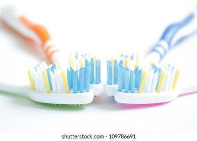 Four very colorful toothbrushes on a white background.
