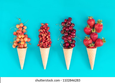 Four waffle cones with red cherries, wild strawberries, yellow cherries, and strawberryes on blue surface. Flat lay, top view sweet food background.