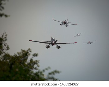 Four water bomber planes flying downward to scoop up more water.