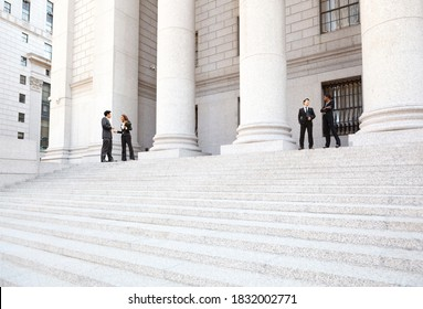 Four well dressed professionals in discussion on the exterior steps of a courthouse. Could be lawyers, business people etc.