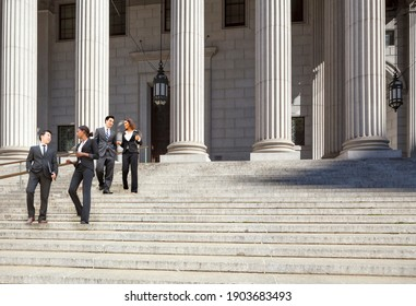 Four well dressed professionals walk down steps in discussion outside of a courthouse. Could be lawyers, business people etc.