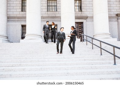 Four well dressed professionals walk down steps in discussion outside of a courthouse or municipal building.. Could be lawyers, business people etc.
