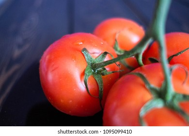 four wet fresh tomatoes on a black plate on a wooden brown retro table/ kitchen