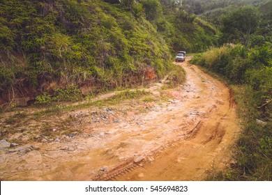 Four wheel drive car going through the muddy road in the Madagascar tropical jungle