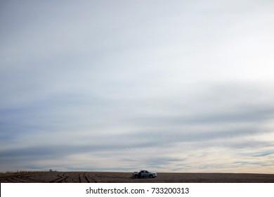 A four wheel drive car in a vast, barren desert landscape under a stormy, overcast sky.