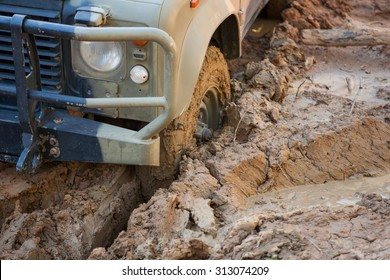 Four wheel drive off road vehicle bogged and stuck up to the axle deep in thick brown mud