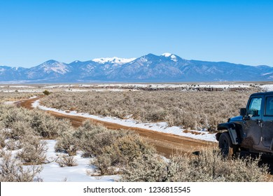 Four wheel drive vehicle on muddy dirt road curving through a sagebrush and snow covered plain with a range of snow-capped mountains in the distance - near Taos, New Mexico
