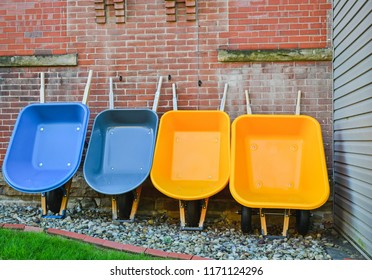 Four wheelbarrows, 2 yellow, 2 blue leaning against a wall
