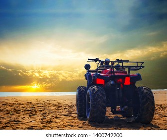 four wheeler dirt bike on sand of sea beach during sunrise with dramatic colorful sky