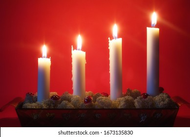 Four white advent candles lit against a red background
