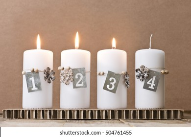four white advent candles with number tags