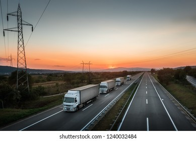 Four White Lorry Trucks Convoy on highway at beautiful sunset