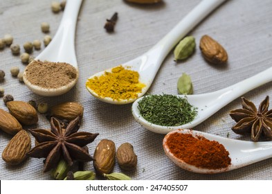 Four white spoons with various spices with almonds, star anise, white pepper and coriander on the grey material