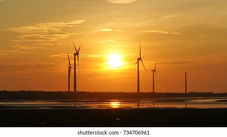 Four white wind wheels with golden light of sunset and mirror of sun is a part of renewable energy at Gaomei westland, Taichung city of Taiwan.