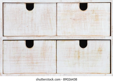 Four white wooden drawers with black holes