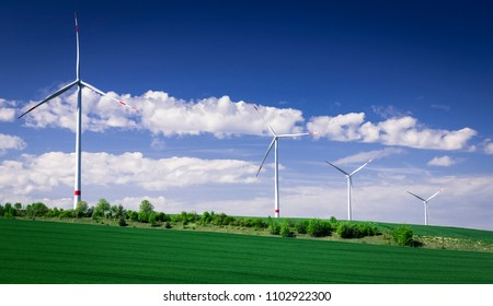 Four wind turbines amidst of green landscape. Recorded in Germany.