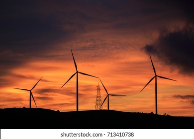 Four wind turbines, sunsets