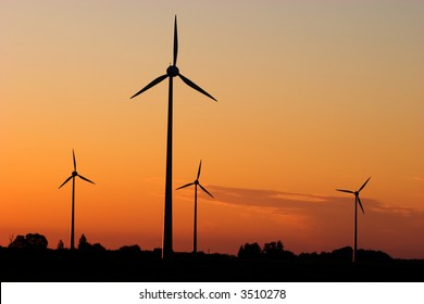 Four windturbines against dramatic sunset producing environment friendly energy