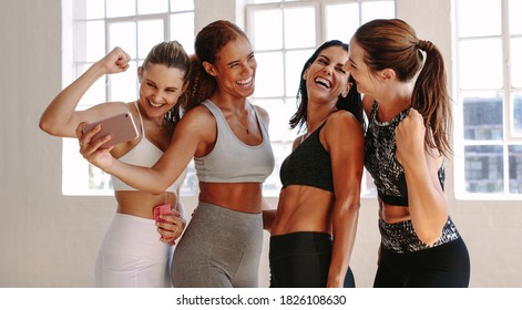 Four women in fitness wear standing together for a selfie after workout. Women laughing and showing muscles while standing for a selfie at a fitness studio.