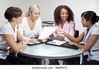 Four women having a business meeting in an office, one African American, one Chinese Asian, One Indian Asian and one Caucasian
