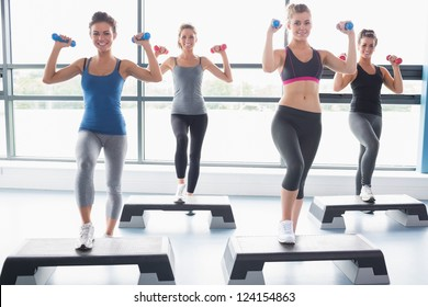 Four women lifting weights while doing aerobics in gym
