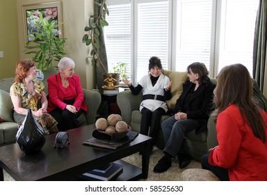 Four women listen on as another shares her ideas.