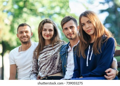 Four women and men sitting on bench in embrace. Happy stylish young friends posing on bench outdoors, smiling and looking at camera. Beautiful healthy people concept