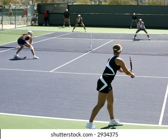 Four women playing doubles at the professional tournament