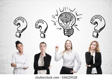 Four women are standing near a concrete wall and looking for a problem solution. Light bulb sketch is drawn above one of them. Question marks. Mock up
