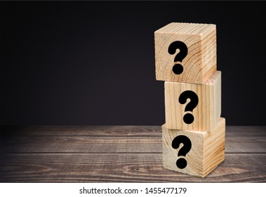 Four wooden blocks with black question marks.          - Image