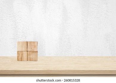 Four wooden cubes on table over white cement wall background