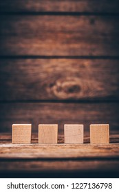 Four Wooden Cubes on Wood Background with Copyspace