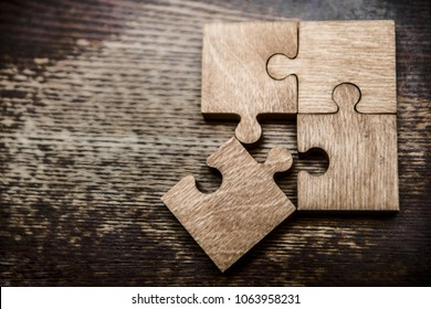 four wooden jigsaw puzzle couple of pieces texture pattern on wood texture background of trunk. empty copy space for inscription or objects. business, education concept