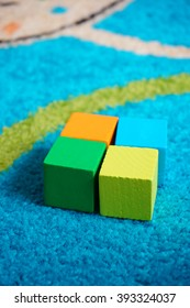 Four wooden toy blocks lying on a carpet