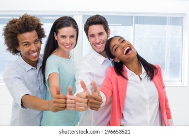 Four workers giving thumbs up and smiling to camera in the office