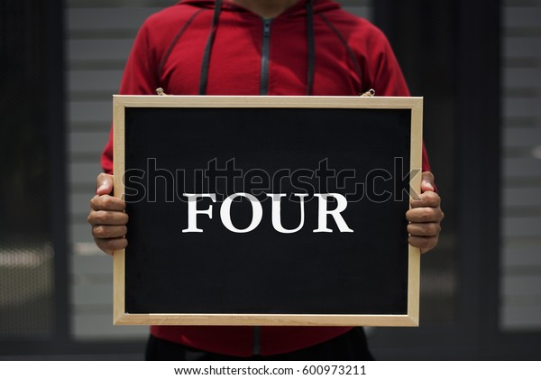 four written on blackboard with someone is holding it