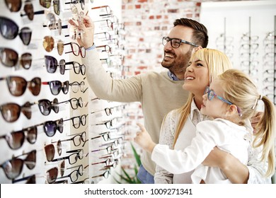 Four year little girl in optics store choosing glasses with her father. Ophtamologist helping.